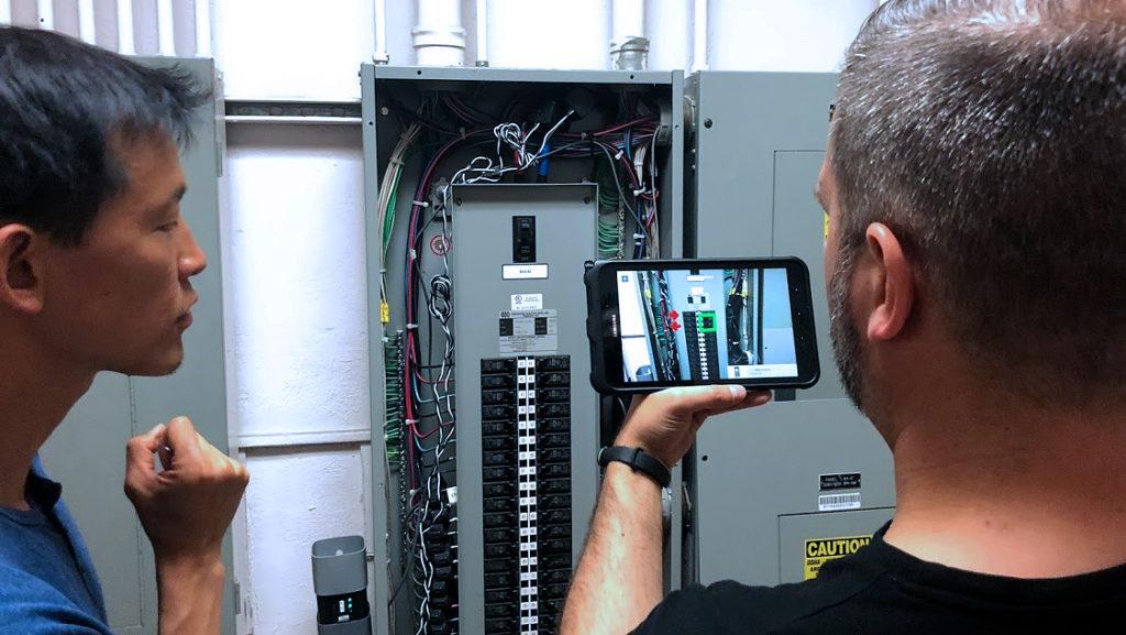 Mauro Rubin e Thomas Chang visualizzano le istruzioni di installazione del misuratore IoT di Verdigris in Realtà Aumentata con l'applicazione BrainPad di JoinPad.